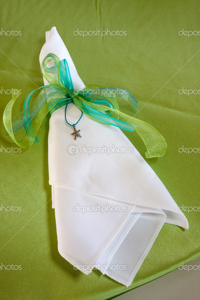 Folded cloth dinner napkin is tied with ribbon and ornamented with a charm starfish. — Stock Photo #1413771