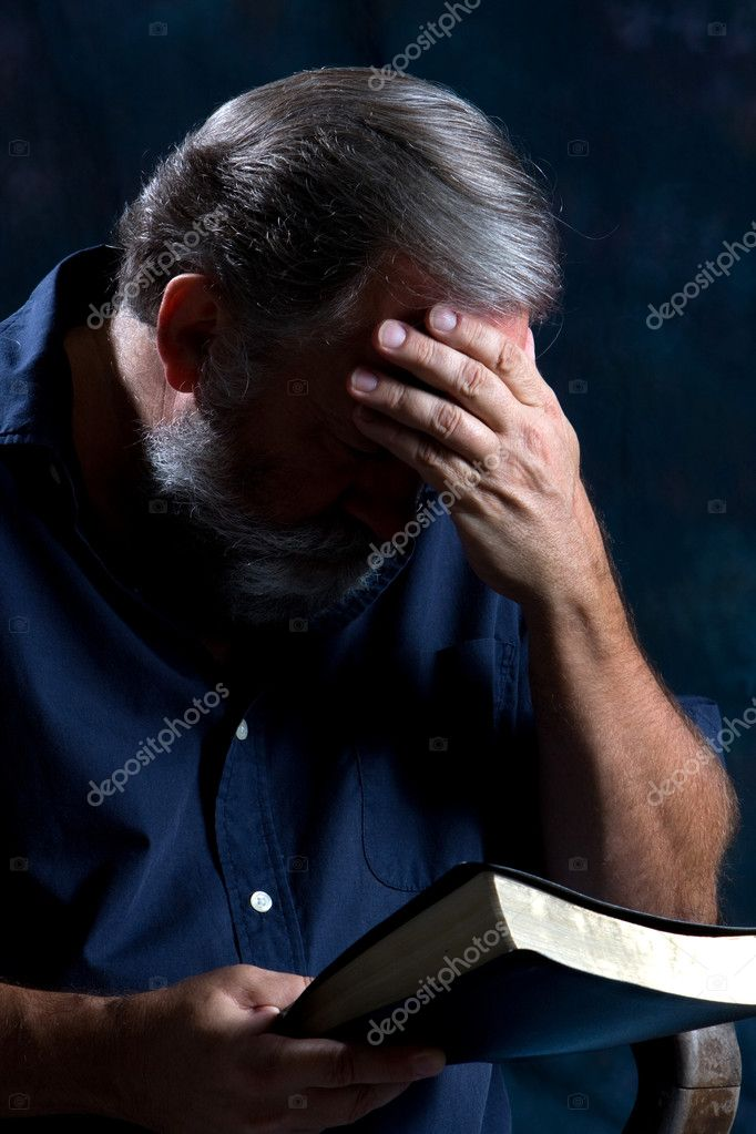 Man holds his head in one hand and bows to pray while holding his bible in the other. — Stock Photo #1413951