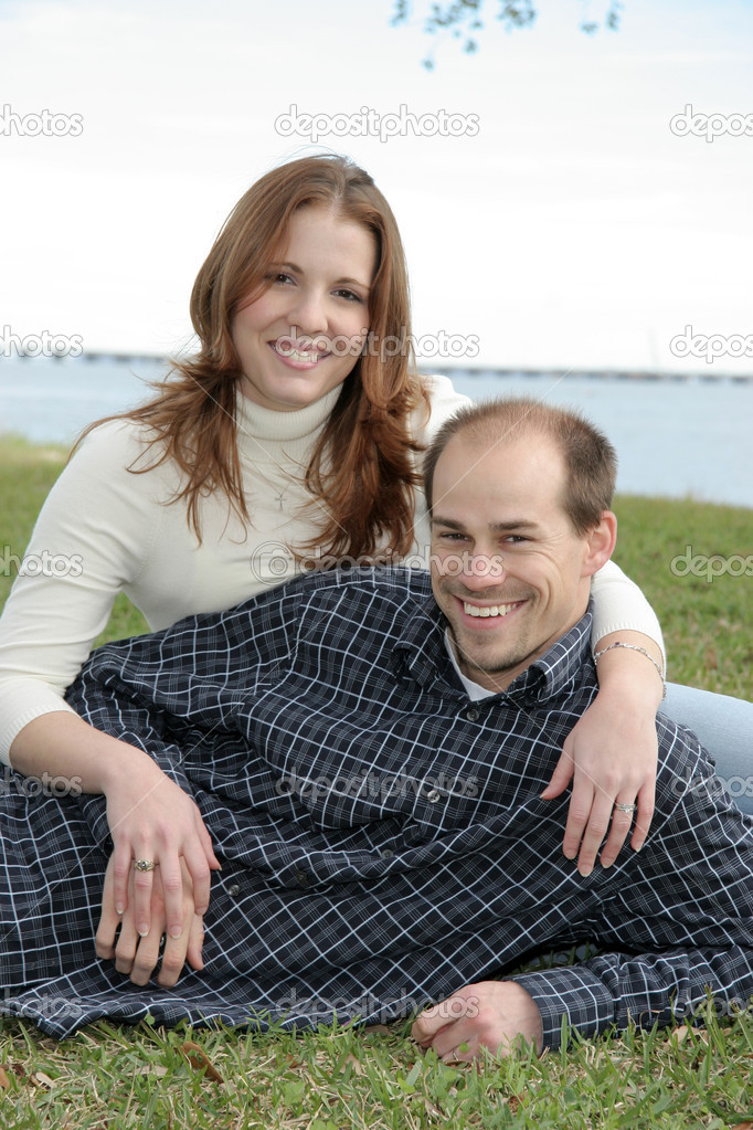 A young married couple sit in the grass enjoying a park setting. — Stock Photo #1414816