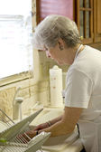 Retiree Washing Dishes In Kitchen — Stock Photo