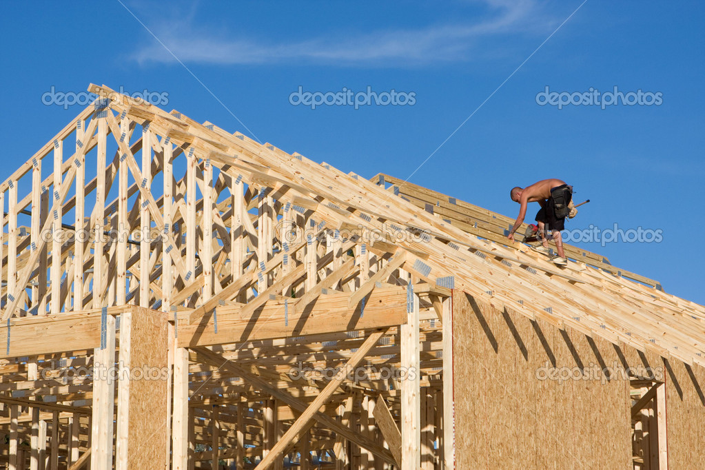 Carpenter uses a pneumatic nail gun to add braces to a truss roof on a new home under construction. — Stock Photo #1439728