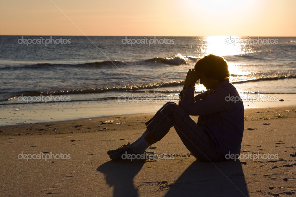 Mature woman sits on the beach with her head bowed and praying as the sun sets on the water. — Stock Photo #1439741
