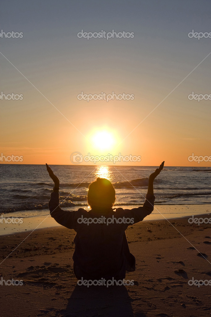 Mature woman sits on the beach with her hands raised as the sun sets on the water. Room for copy at top.  Stock Photo #1439756