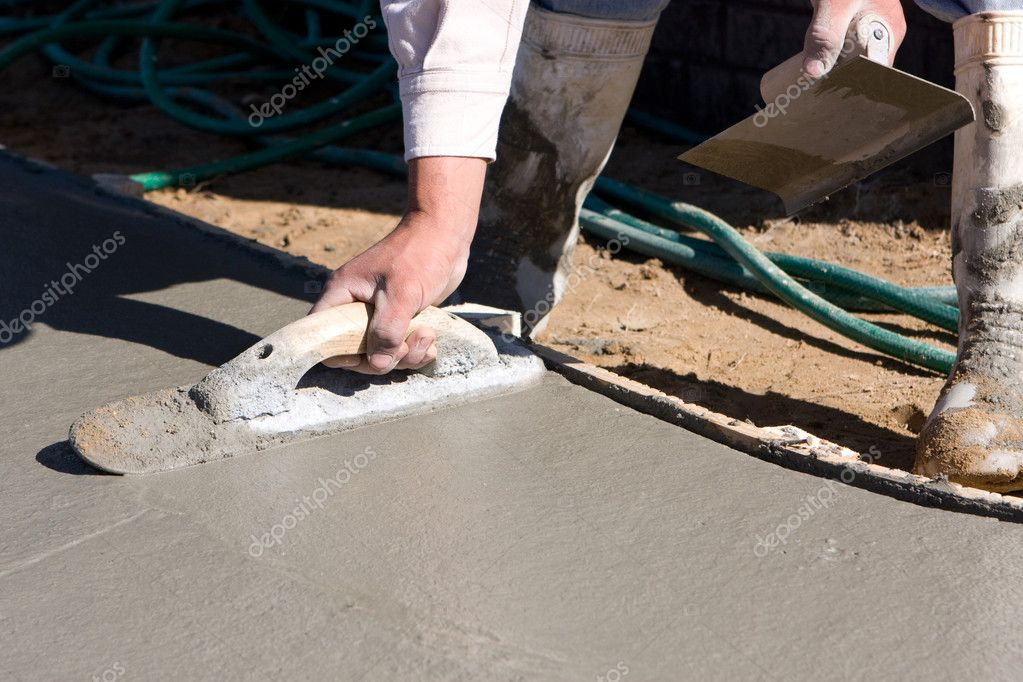 Concrete finisher uses a float and an edger to smooth and finish the surface of a concrete sidewalk.  Foto de Stock   #1619657