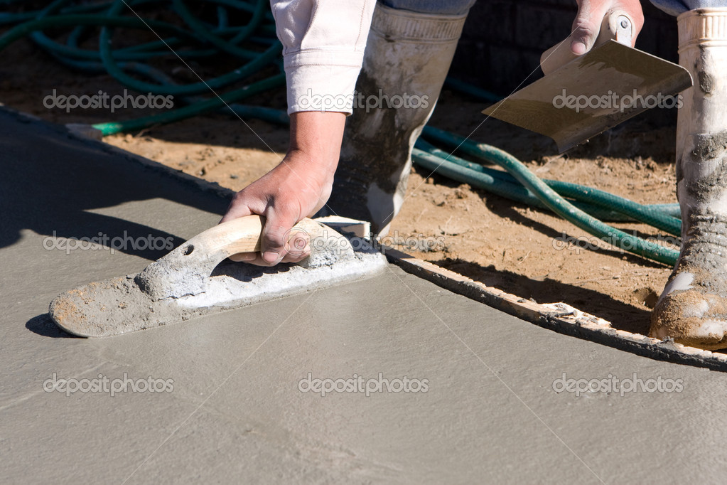 Concrete finisher uses a float and an edger to smooth and finish the surface of a concrete sidewalk.  Stockfoto #1619657