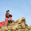 Man in Mongolian costume on rock — Stock Photo #1406679