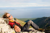 Man relaxing at mountain top — Stock Photo