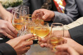 Glasses with champagne in hands being clinked during drinking toast — Stock Photo