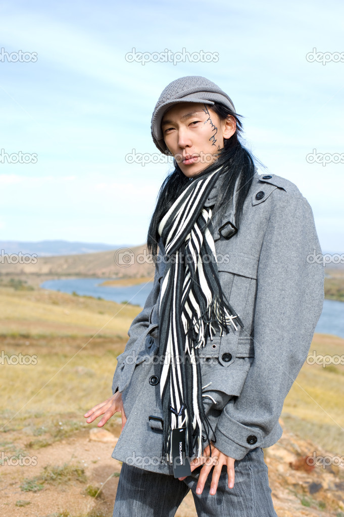 Young asian man in grey coat, cap and striped black-and-white scarf. The tracery on his cheek is his name Chinghis in ancient Mongolian. — Stock Photo #1407013