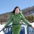 Girl in green ski costume — Stock Photo