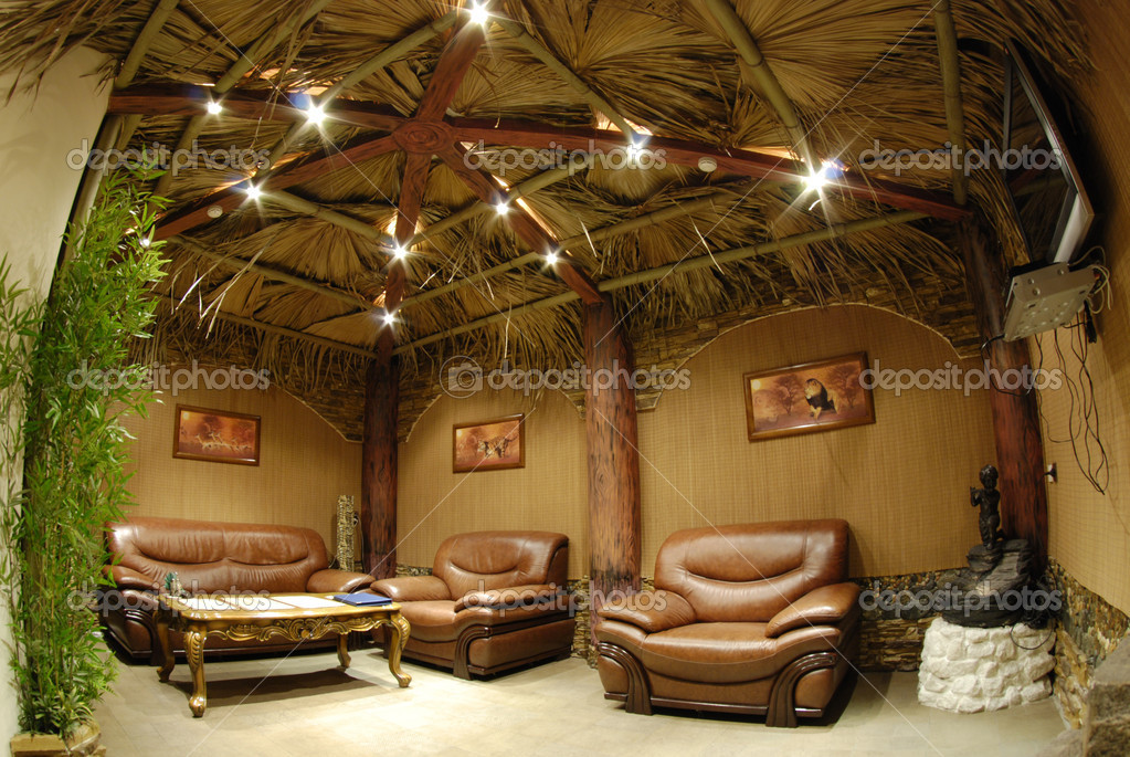 Relaxation room in sauna with nice massive leather brown furniture (sofa and two armchairs) and wooden carved polished coffee table on curved legs. By contrast, — Stock Photo #1425845
