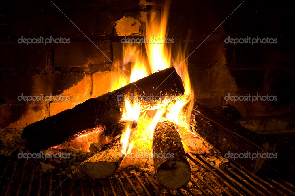 Burning round logs in fireplace against brick smoked wall — Stock Photo #2040245