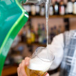 Filling glass with beer from faucet - Stock Photo