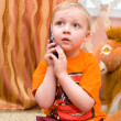 Little kid speaks over cell phone - Stock Photo