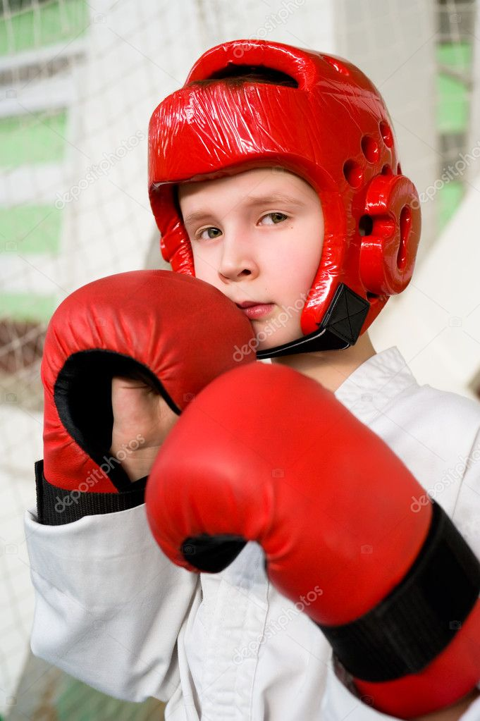 Caucasian boy in red helmet and gloves making taekwondo punch into camera — Stock Photo #2451975
