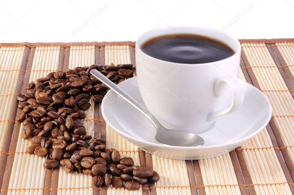 White cup with cofee on bamboo mat and coffee beans — Stock Photo #1442568