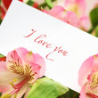 Card in flowers with love words — Stock Photo