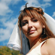 Young bride and blue sky — Stock Photo