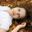 Girl with blue eyes lying in the leaves — Stock Photo