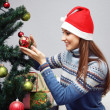 Girl decorating Christmas tree — Stock Photo #1508803