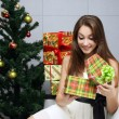 Opening gift near the Christmas tree — Stok fotoğraf