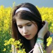 Beautiful girl portrait at canola — Stock Photo