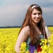 Smiling girl at the rape field — Stock Photo