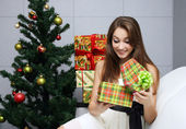 Opening gift near the Christmas tree — Stock Photo