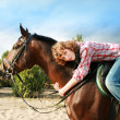 Smiling girl on her horse - Stock Photo