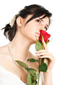 Bride sniffing a red rose — Stock Photo