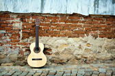 Guitar on old wall — Stock Photo