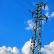 A tall electric pillar in the blue sky — Stock Photo