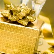 Gift box with golden ribbon - Stock Photo
