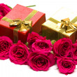 Golden gift boxes with red roses — Stock Photo