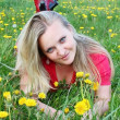 Young girl on dandelion meadow — Stock fotografie