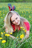 Young girl on dandelion meadow — ストック写真