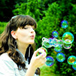 Stock Photo: Young girl blowing soap bubbles