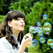 Young girl blowing soap bubbles — Stock fotografie