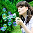 Attractive girl blowing soap bubbles — Stockfoto