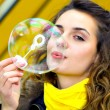 Stock Photo: Smile teen blowing soap bubbles
