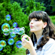Young girl blowing soap bubbles — Stock Photo