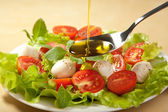 Olive oil pouring over salad — Foto Stock