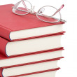 Stack of red books with eyeglasses — Stock Photo