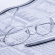 Newspaper with glasses and pen — Stock Photo