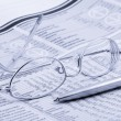 Newspaper with glasses and pen - Stock Photo