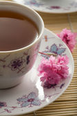 Cup of tea and flowers over bamboo mat — Stock Photo