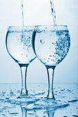 Pure water splashing into two glasses — Stock Photo