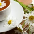 Cup of herbal tea and camomile flowers - Stock Photo