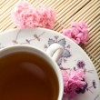 Cup of tea and flowers over bamboo mat - Stock Photo