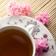 Stock Photo: Cup of teand flowers over bamboo mat